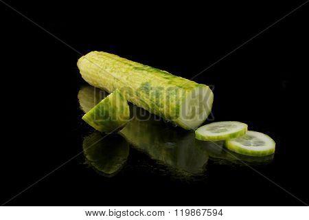 A Cucumber Cut On Black Background