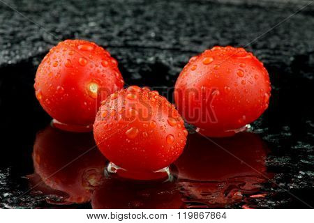 Three Tomatoes With Water On Black Background