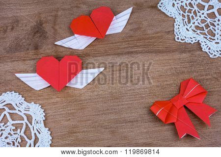 Origami hearts with wings on a wooden background with lace. Two hearts.