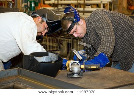 Two welders working together on a difficult metal work project.  Authentic and accurate content depiction in compliance with industry code and safety standards.