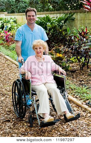 Disabled senior woman in a wheelchair with her male nurse companion.