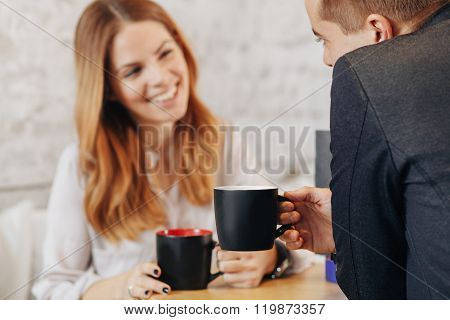 Selective Focus On A Cup Of Coffee With Happy Young Couple Out Of Focus Drinking Coffee In A Cafe
