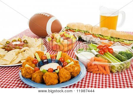 Table spread with appetizer trays for the footbal party.  Horizontal view over white background.