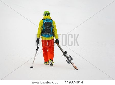 Sad and weary skier goes away, dragging skis.