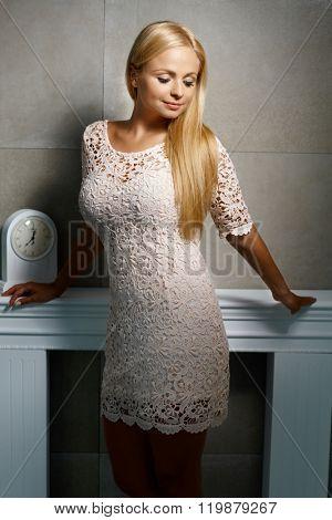 Sensual blonde woman in mini dress posing over grey wall.
