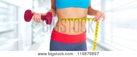 Woman abdomen with measuring tape over blue background.