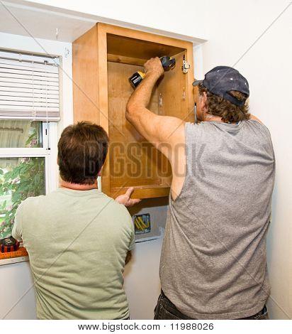 Carpenter and helper installing kitchen cabinets together.