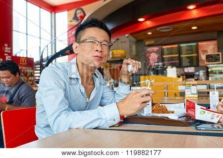 PATTAYA, THAILAND - FEBRUARY 25, 2016: man eat at McDonald's restaurant. McDonald's primarily sells hamburgers, cheeseburgers, chicken, french fries, breakfast items, soft drinks, milkshakes, desserts