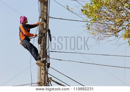 SAI YOK, THAILAND, JANUARY 22, 2016 :  A technician is repairing or checking the messy electrical network in the city of Sai Yok, Thailand