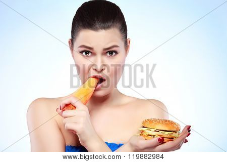 Funny girl eating hamburger on grey background