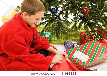 Cute little boy opening his presents on Christmas morning.