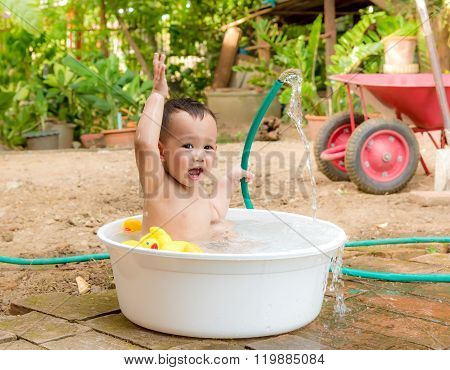 Asian Baby Boy Outdoor Bathing In The White Bathtub . He Is Smiling And Playing Yellow Duck