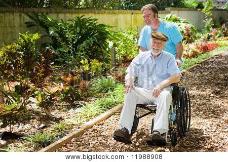 Disabled senior man being pushed through a lovely garden by his nurse.