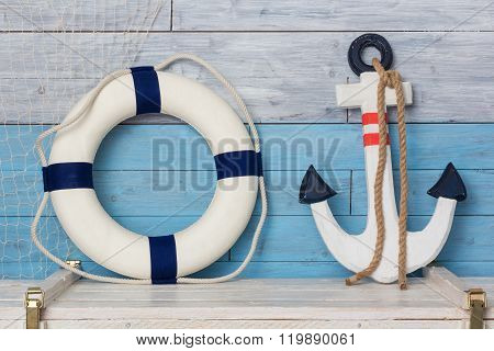 Anchor and life buoy on wood background blue-white