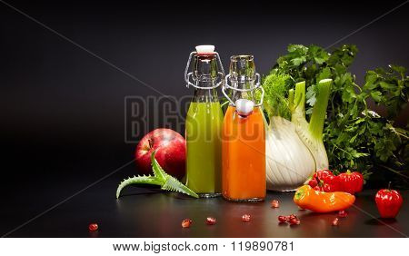 Bottles and Glasses with fresh organic vegetable and fruit juices isolated on black. Detox diet.