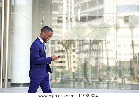 Young Businessman Walking And Using Cell Phone