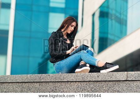 Girl surfing on tablet against city background