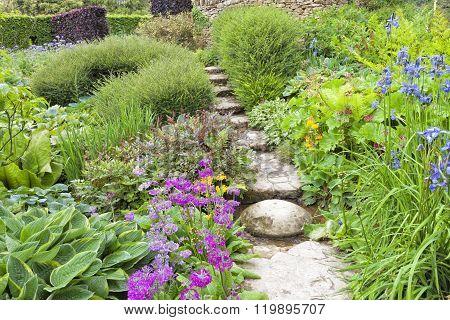 Cottage flowering garden with stone walkway