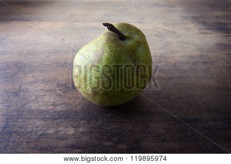 Pear on rustic wooden table. low key.