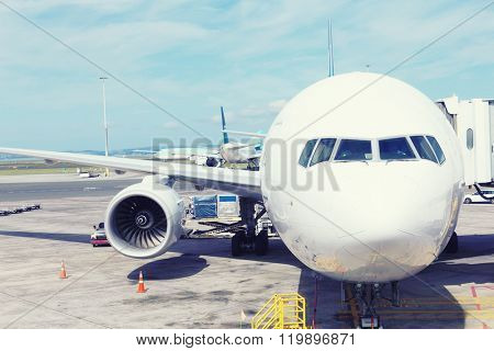 white airplane in apron in cloudy sky