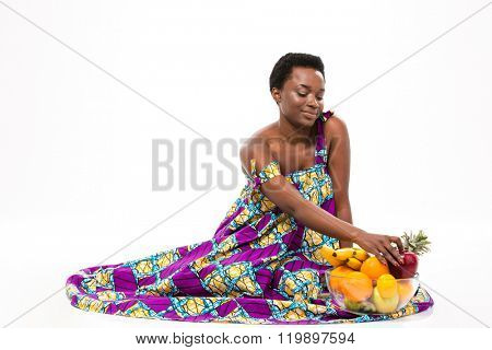 Smiling charming african american young woman in bright sundress sitting with glass bowl of fruits over white background