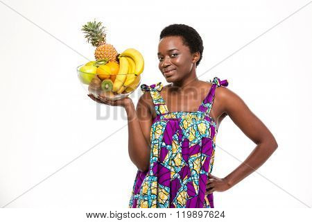 Cheerful attractive african american young woman in bright sundress standing and holding glass bowl with fruits over white background