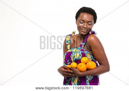 Sensual attractive african american young woman in bright sundress holding citrus fruits over white background