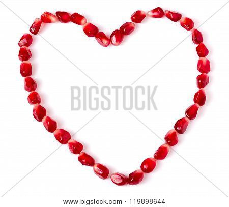 Heart symbol made from pomegranate seeds isolated on white background
