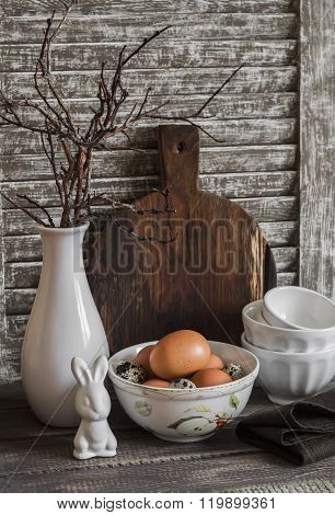 Easter Kitchen Still Life - Eggs In A Bowl, A Vase With Dry Twigs, Ceramic Rabbit, Vintage Crockery