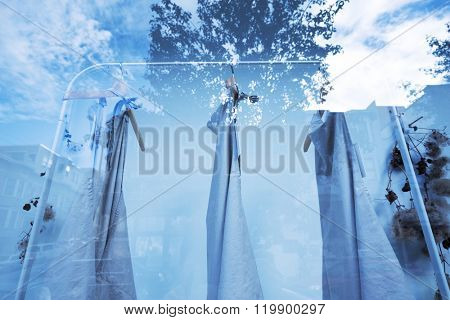shop display window with clothes and reflection of cloud