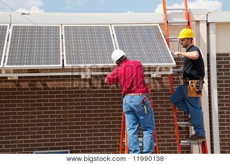 Two electricians installing solar panels on a building.