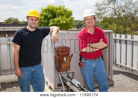 Two air conditioning repair techs standing on a roof in front of an industrial compressor unit.