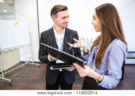 Two smiling businesspeople talking and working together in office