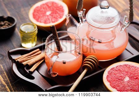 Fruit herbal tea with spices and honey in a glass teapot and cup Dark wooden background