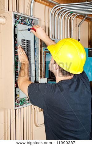 Electrician working on a breaker panel in a control room filled with exposed pipe.