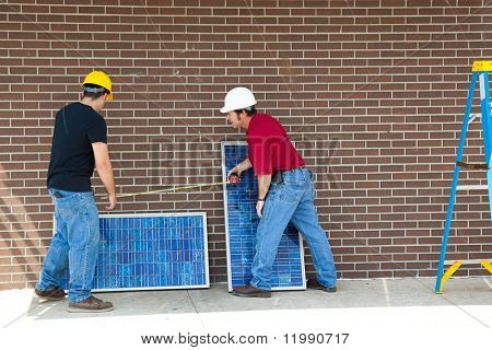 Workers measuring and installing solar electric panels.