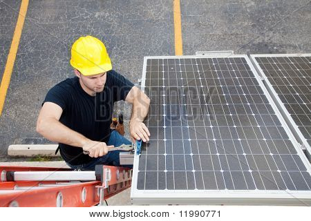 Electrician repairing solar panel.  Wide angle view with room for text.
