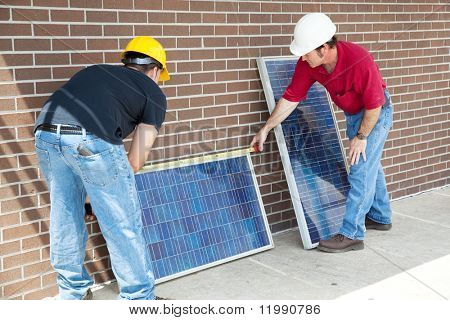 Electricians measuring solar panels prior to installing them.
