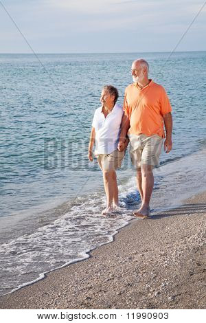 Retired senior couple takes a romantic stroll on the beach.