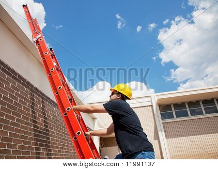 Construction worker climbing up to the roof of a building.  Wide view with lots of room for text.