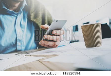 Businessman in modern office. Texting message smartphone. Wood table, craft take away cup. Horizonta