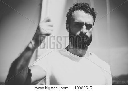Portrait of young bearded man standing on the yacht in sunny day. Horizontal mockup, black and white