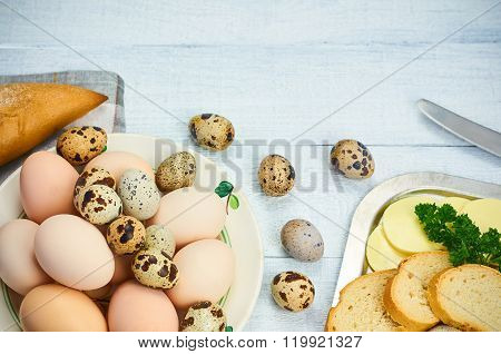 Quail eggs and hen egg with bread and butter