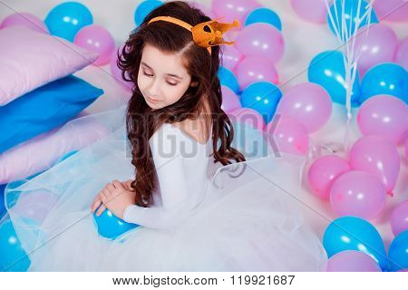 Cute little princess girl sitting among balloons in room over white background. Looking at camera. C