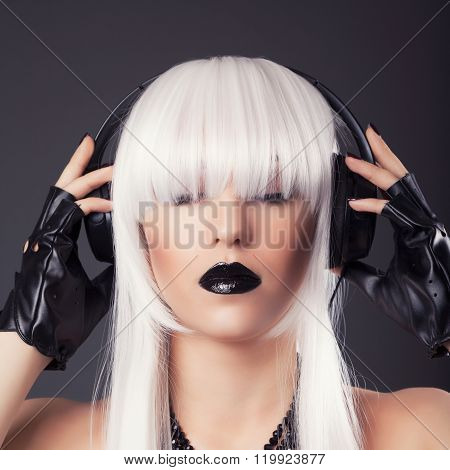 Beautiful Blonde Woman With Black Make-up And Accessories Listening To Music