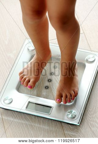 Barefoot Woman Standing On A Bathroom Scale