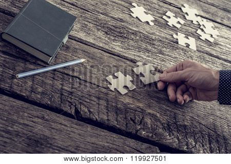 Hand Of A Businessman Matching Two Puzzle Pieces