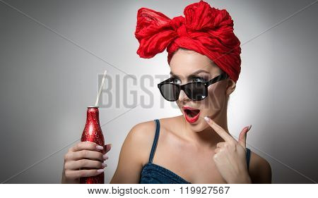 Woman with red turban and sunglasses holding a drink bottle with a straw inside