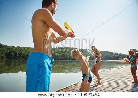 Happy family with children spraying water to each other at the lake