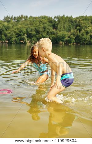Two children playing with a frisbee in the water in summer